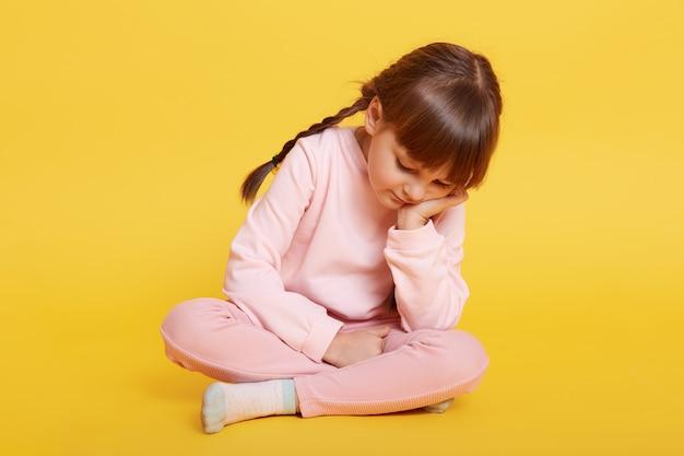 Piccola ragazza caucasica infelice che si siede sul pavimento sopra colore giallo