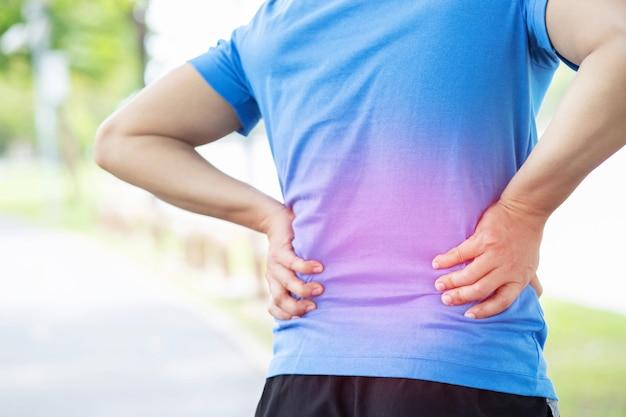 Uomo infelice che soffre di infortunio sportivo durante l'esercizio fisico, con lombalgia alla colonna vertebrale con mal di schiena.