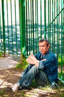 L'uomo infelice con le braccia incrociate si siede a terra