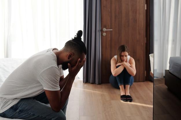 Marito e moglie offesi infelici seduti in camera da letto separati l'uno dall'altro dopo un grande litigio o lotta, il divorzio e il concetto di problemi di relazione