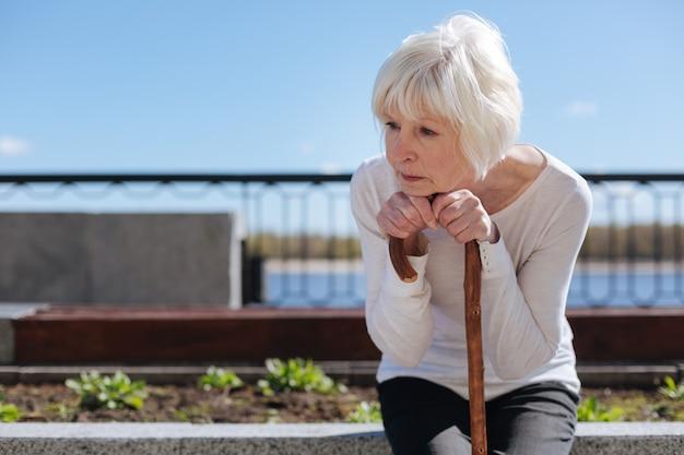 Donna invecchiata piacevole infelice che mette la testa sulle mani e tiene d'occhio gli uccelli