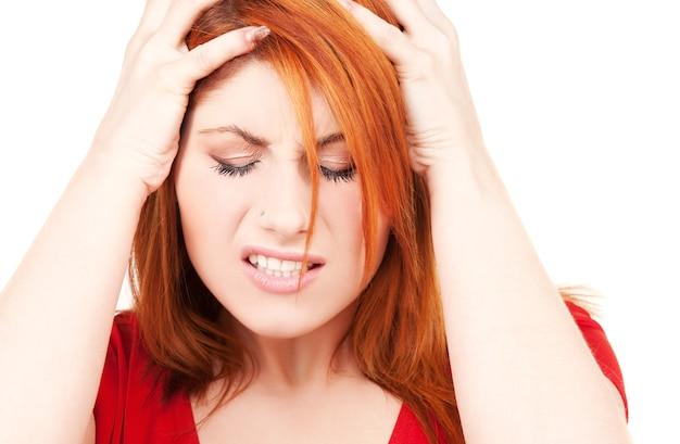 Donna infelice rossa sul muro bianco