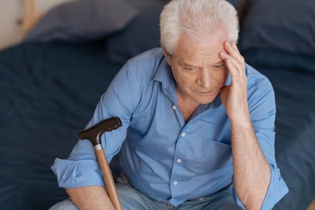 Uomo invecchiato triste infelice che si siede sul letto e tocca la sua testa mentre pensa al suo passato