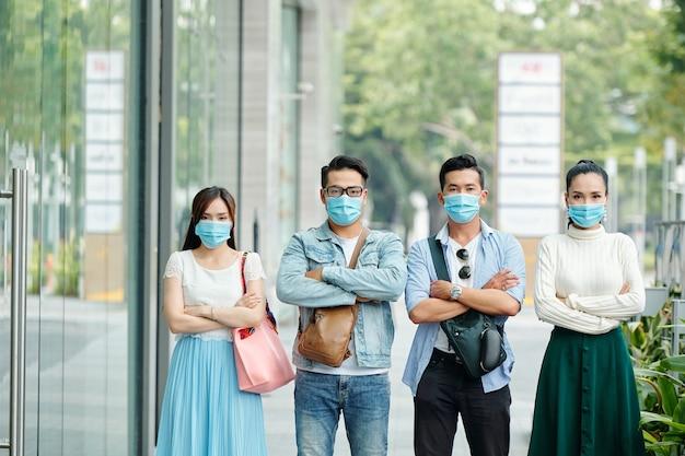Giovani vietnamiti seri infelici in maschere mediche in piedi in strada con le braccia conserte e guardando la fotocamera