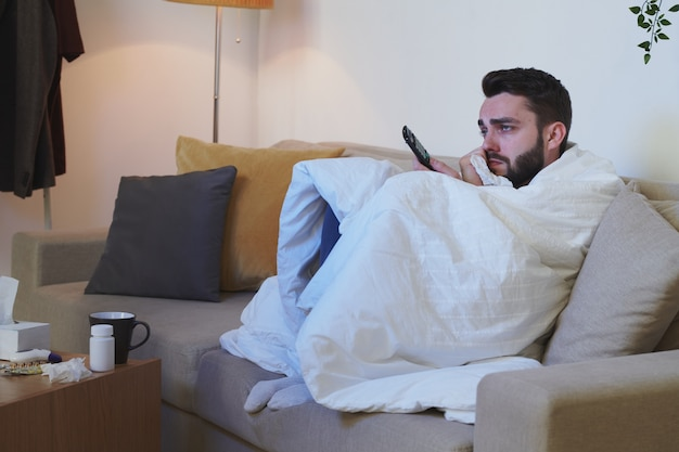 Uomo infelice e malato avvolto in una coperta seduto sul divano davanti al televisore e guardare film mentre si è a casa per autoisolamento