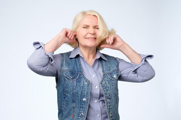 Femmina senior stressata infelice che fa fronte ironico, tappando le orecchie con le dita