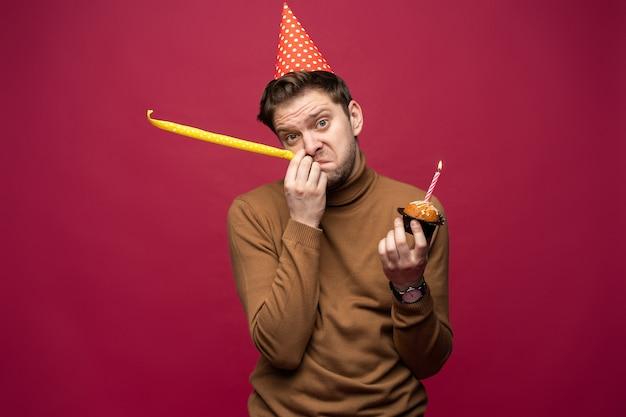 Giovane stressato infelice con il bigné di compleanno che ha sguardo infelice
