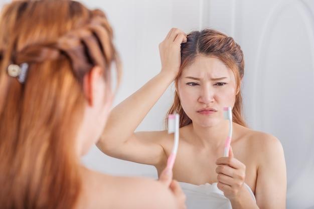Donna infelice in telo da bagno lavarsi i denti con specchio in bagno