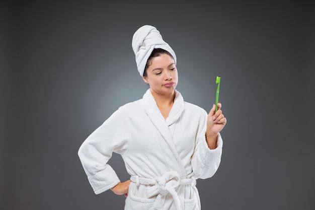 La donna infelice in un accappatoio e un asciugamano avvolto intorno alla testa tiene in mano uno spazzolino da denti