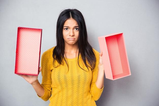 Donna infelice che tiene il contenitore di regalo vuoto