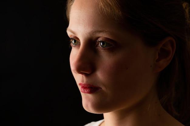 Donna infelice che osserva senza sorriso su priorità bassa nera