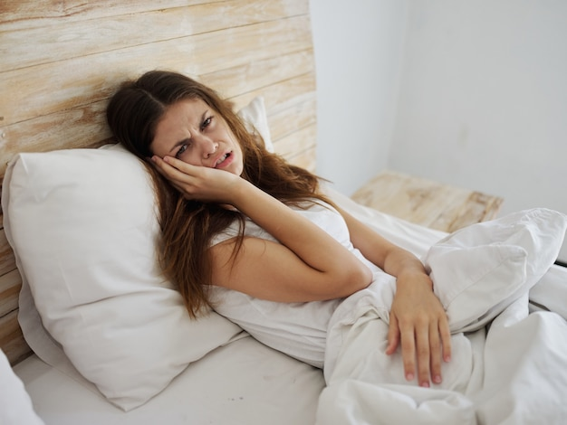 Donna infelice sdraiata a letto che si sente male problemi di salute