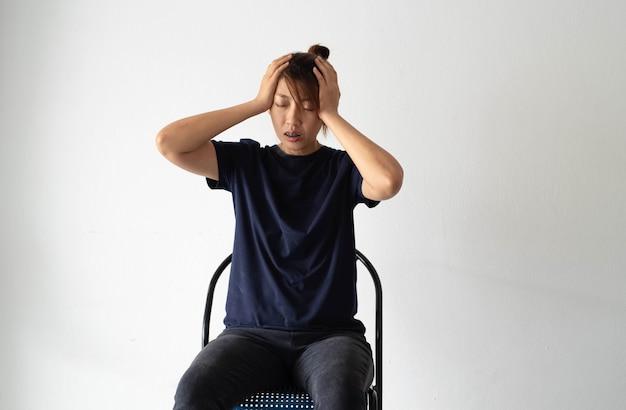 La donna infelice che si siede contro sulla parete, solleva le mani tocca la testa, nervosa, turbata e stress