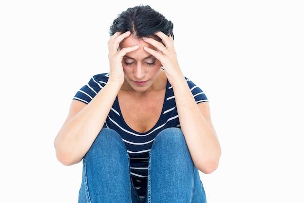 Donna infelice che si siede sul pavimento