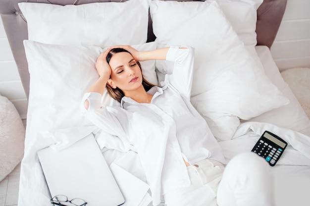 Una ragazza infelice ha ricevuto un avviso di debito bancario o sfratto, sentirsi male sdraiata sul letto, cattive notizie, mal di testa