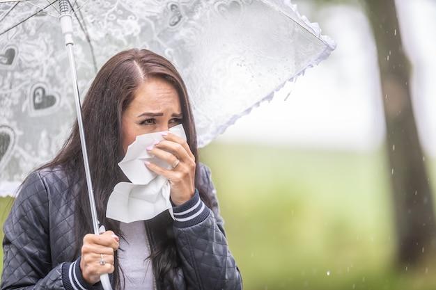 Infelice giovane donna starnutisce in un tovagliolo snaitary, avendo freddo in una giornata piovosa fuori, tenendo l'ombrello.