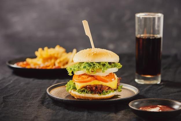Concetto malsano. cibo malsano: hamburger, salsa, patate, cola.