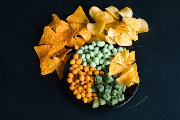 Spuntini malsani degli alimenti a rapida preparazione. cattive abitudini alimentari. assortimento di arachidi piccanti patatine salate e crostini di pane su un piatto