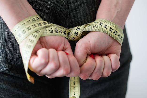Metodi dimagranti malsani. mani di donna legate con nastro di misurazione dietro la schiena