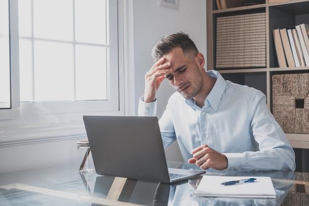 Uomo d'affari stressato malsano che si toglie gli occhiali, si sfrega le palpebre, soffre di sindrome degli occhi asciutti a causa del lungo superlavoro del computer, massaggia il ponte della testa per alleviare il dolore in ufficio a casa.
