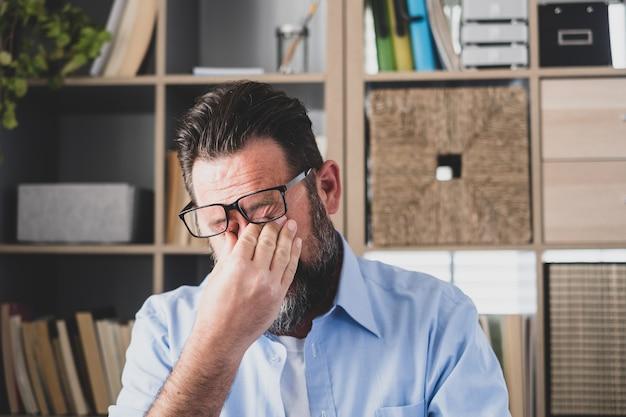 Uomo d'affari stressato malsano che si toglie gli occhiali, si sfrega le palpebre, soffre di sindrome degli occhi asciutti a causa del lungo superlavoro del computer, massaggia il ponte del naso alleviando il dolore in ufficio a casa