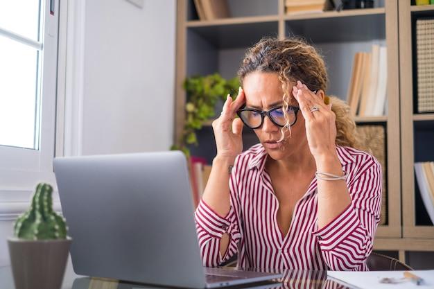 Donna d'affari stressata e malsana che si toglie gli occhiali, si sfrega le palpebre, soffre di sindrome degli occhi asciutti a causa del lungo superlavoro del computer, massaggia il ponte della testa per alleviare il dolore in ufficio a casa.