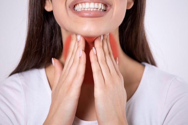 La donna malsana tocca il collo sente sentimenti dolorosi di disagio. irritazione del dolore alla gola irritata
