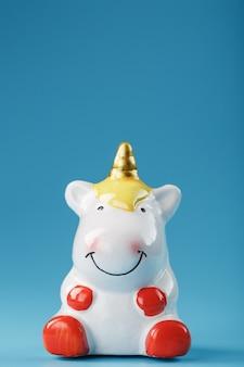 Statuetta di unicorno su sfondo blu con spazio libero