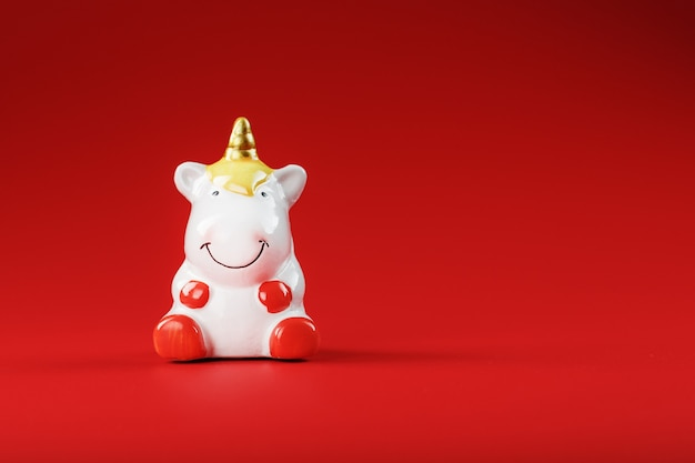 Statuetta di unicorno su uno sfondo rosso con spazio libero.