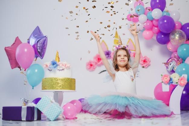 Unicorn girl lancia coriandoli. idea per decorare la festa di compleanno in stile unicorno. decorazione unicorno per ragazza festaiolo