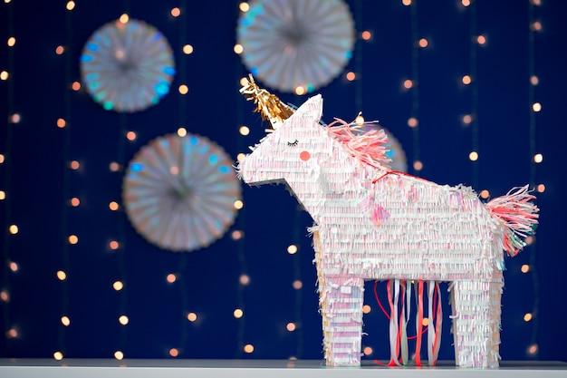 Pinata festa unicorno su sfondo blu bokeh si chiuda