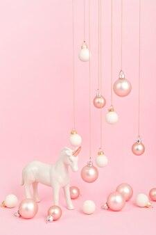 Unicorno con ornamenti natalizi sulla superficie rosa