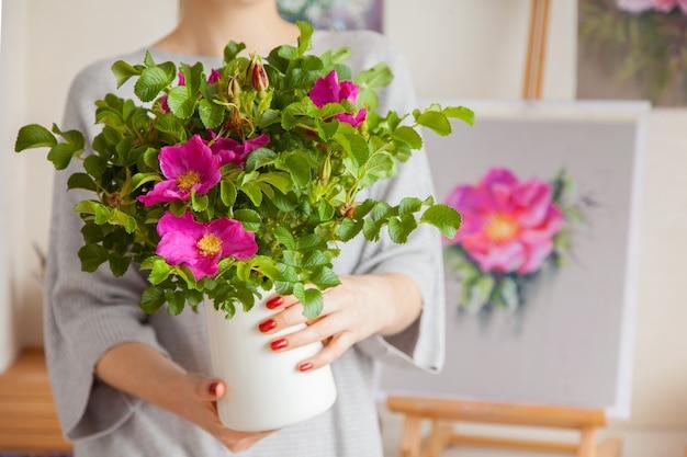 Una giovane donna sfocata non identificata tiene un vaso nelle sue mani con una bella rosa canina in fiore rosa. il concetto di decorazione d'interni e piante da allevamento