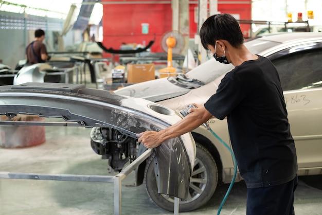 Un dentista non identificato o un tecnico meccanico automobilistico controlla e corregge la carrozzeria e la parte del corpo del paraurti in fibra