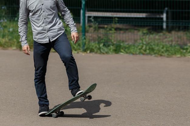 Skateboarder maschio giovane ed elegante non identificato che si prepara a cavalcare lo sketchboard sollevandolo con un piede nel parco nelle calde giornate estive, copyspace