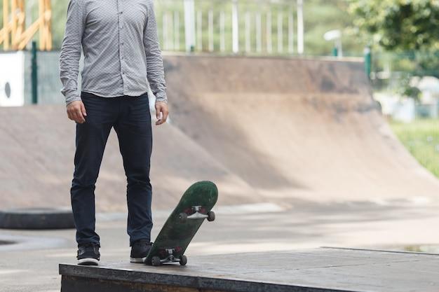 Skateboarder maschio giovane ed elegante non identificato che si prepara a cavalcare lo sketchboard sollevandolo con un piede nel parco nelle calde giornate estive
