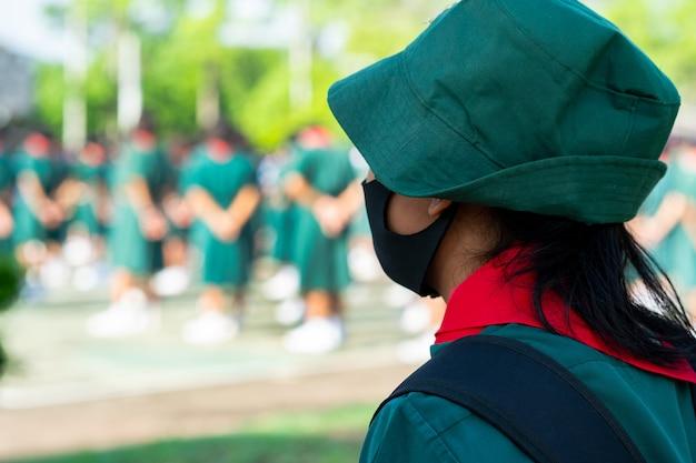 Studenti scout uniformi che indossano maschere facciali