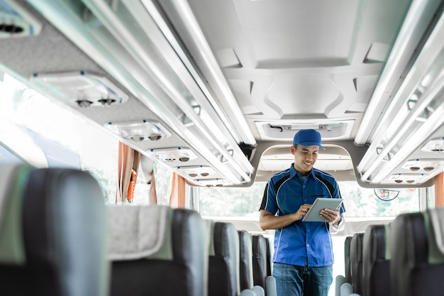 Un membro dell'equipaggio dell'autobus in uniforme utilizza una tavoletta digitale mentre controlla i biglietti online mentre si trova sull'autobus