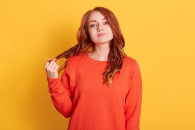 Donna attraente indifferente non impressionata con capelli rossi