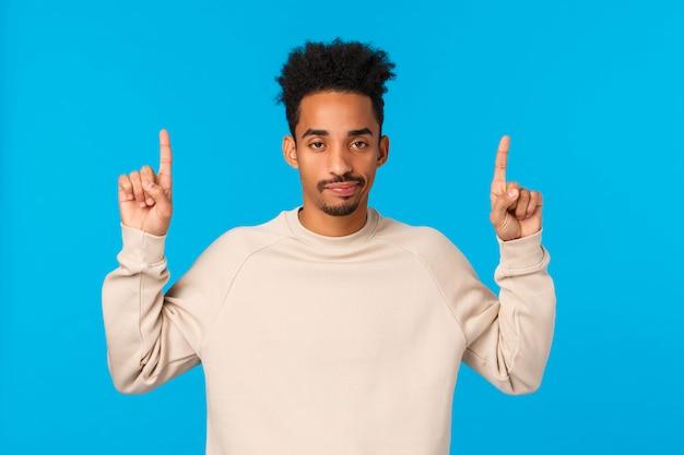 Maschio hipster afroamericano moderno di bell'aspetto non impressionato, scettico con taglio di capelli afro, baffi, dita rivolte verso l'alto, aspetto indifferente e disattento, non piacciono i regali, parete blu