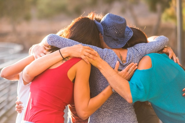 Unione tutti insieme come un lavoro di squadra e un gruppo di amiche femmine 7 belle donne si abbracciano tutte insieme sotto la luce del sole e il tramonto per amicizia, relazione e concetto di successo. amici senza tempo.