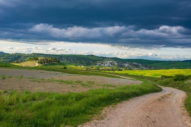 Paesaggio verde unico in val d'orcia, toscana, italia. drammatico cielo al tramonto, strada sterrata che attraversa la gamma di colline coltivate e campi di cereali.