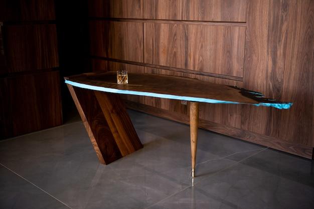 Tavolo unico in legno duro con un bicchiere di whisky