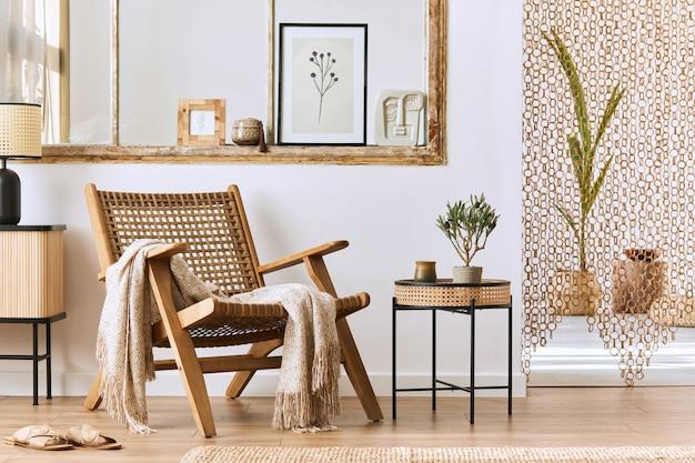 Interno unico del soggiorno con elegante poltrona in rattan, mobili di design, fiori secchi, cornice per poster, pavimento in legno, decorazioni ed eleganti accessori personali