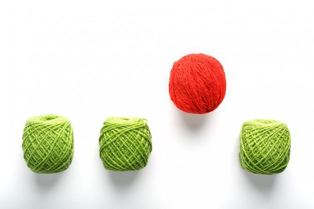 La palla rossa unica salta da una fila di palle di lana identiche