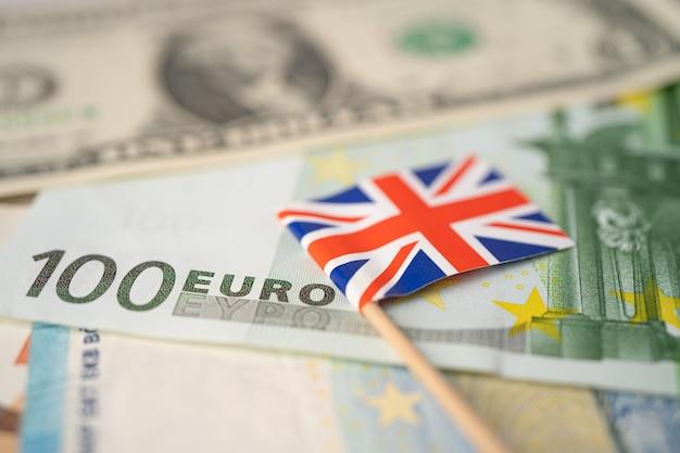 Bandiera del regno unito con banconote in dollari ed euro; conto bancario, economia dei dati di ricerca analitica degli investimenti, commercio, concetto di società di affari.