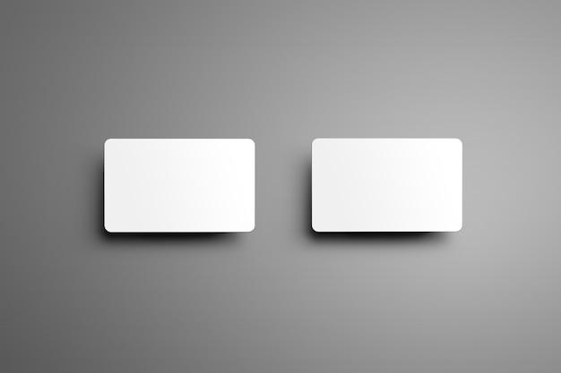 Due carte regalo universali bancarie con ombre isolate su uno sfondo grigio. vista dall'alto.