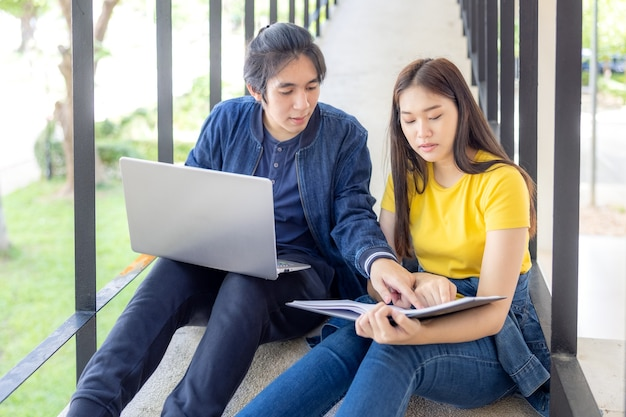 Nel campus universitario, due coppie asiatiche si siedono sulle scale con i pollici in su, lavorando sui laptop.