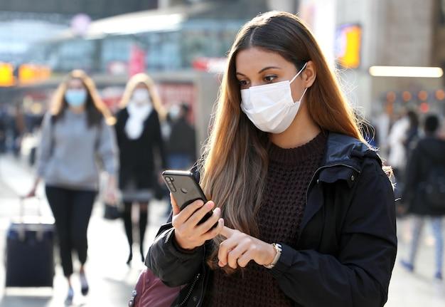 Studente universitario pendolare a piedi utilizzando il telefono cellulare che indossa la protezione della maschera