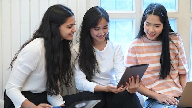Studente universitario che fa il gruppo di e-learning usando una compressa del computer e sedendosi insieme al pavimento del salotto